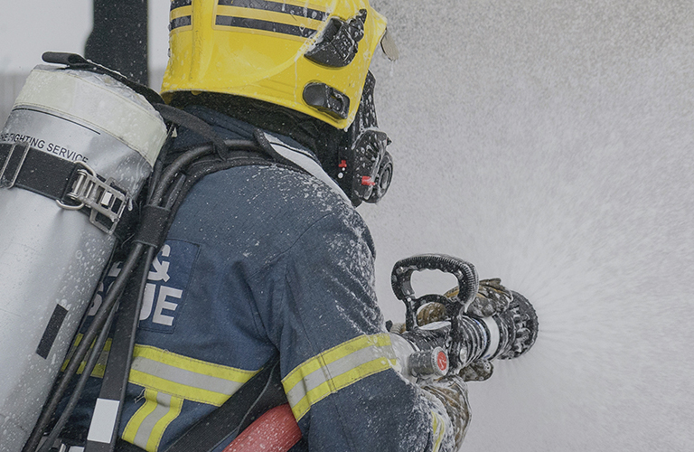 Firefighter wearing Savox gear extinguishing fire.